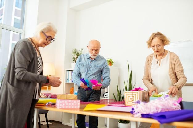 Une activité tellement intéressante. gens créatifs sympas s'amusant tout en étant engagés dans l'emballage de cadeaux