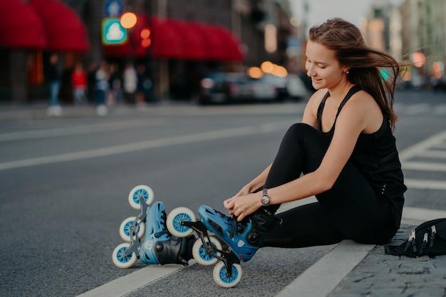 Les activités de plein air correspondent au style de vie. plan latéral d'une femme active assise sur la route ajuste les patins à roues alignées se prépare pour le patinage met des patins à roues alignées a les cheveux flottant au vent aime son passe-temps favori du week-end
