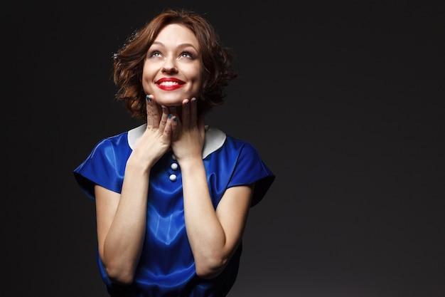 Actrice fille en costume de scène bleu avec des cheveux roux et du maquillage sur fond noir à la recherche