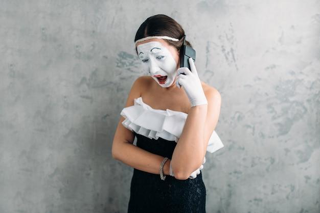 Actrice mime jouant avec un téléphone mobile. artiste féminine de comédie posant