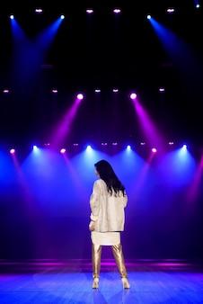 Actrice sur scène dans des faisceaux lumineux colorés.