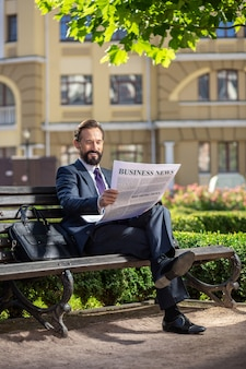 Actualité économique. homme d'affaires souriant optimiste, lisant un journal tout en se reposant sur le banc