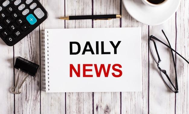 L'actualité quotidienne est écrite dans un bloc-notes blanc près d'une calculatrice, d'un café, de verres et d'un stylo