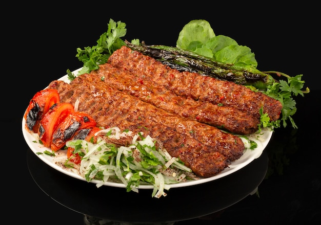 Adana kebab servi avec légumes et poivrons grillés et tomate
