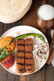 Adana kebap turc avec riz pilaf et légumes servis sur une assiette