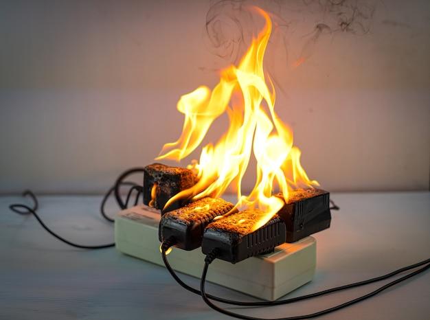 Sur l'adaptateur d'incendie à la prise de courant sur fond blanc court-circuit électrique