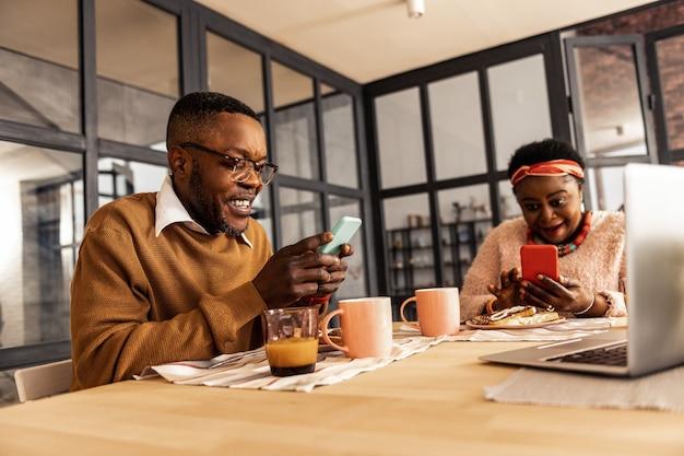 Addiction à internet. heureux couple joyeux ne se parlant pas tout en étant engagé dans leurs smartphones