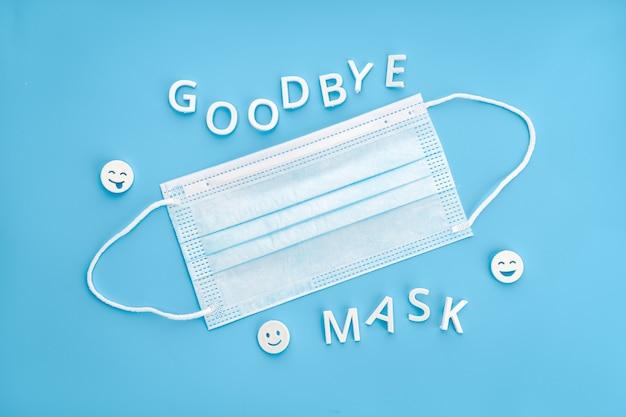 Adieu phrase de masque et masque facial isolé sur fond bleu. concept de ne plus être obligé de porter des masques faciaux
