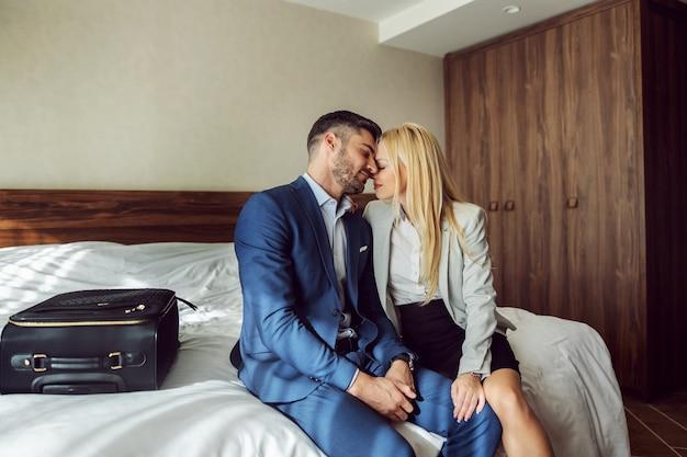 Un adieu triste et déchirant au bout de la route. couple d'affaires disant au revoir sur le lit dans une chambre d'hôtel. les câlins et les câlins aiment la distance, au revoir baiser
