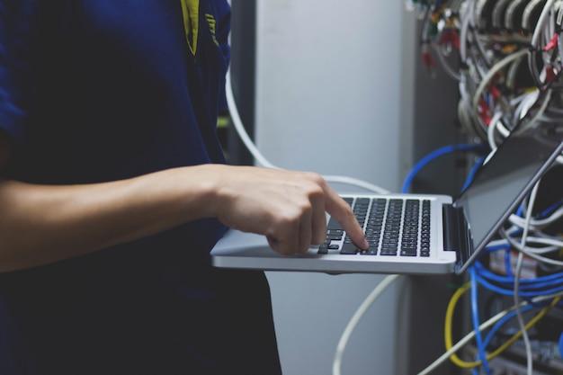 Administrateur technicien tapant sur son ordinateur portable dans la salle du centre de données
