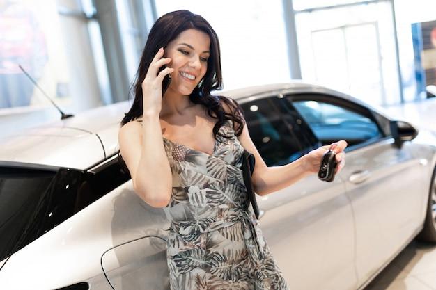 Admirable brunet parlant au téléphone et possédant près de sa nouvelle voiture dans la salle d'exposition du concessionnaire