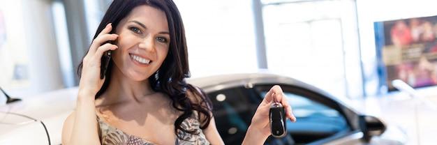 Admirable brunet parle au téléphone et pose près de sa nouvelle voiture dans le showroom du concessionnaire