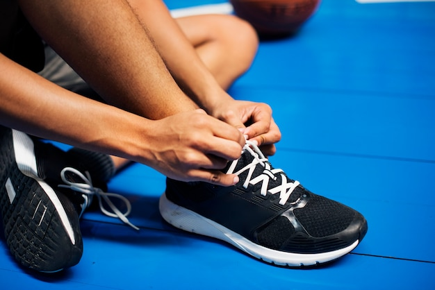 Un adolescent afro-américain attachant ses lacets sur un terrain de basket