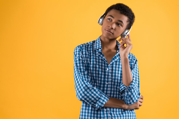 Adolescent afro-américain au casque écoute de la musique.