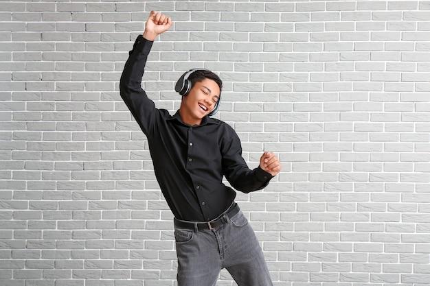Adolescent afro-américain dansant et écoutant de la musique contre le mur de briques