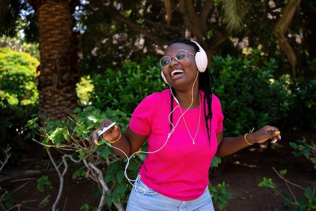 Adolescent afro-américain écoutant de la musique avec des écouteurs et un mobile