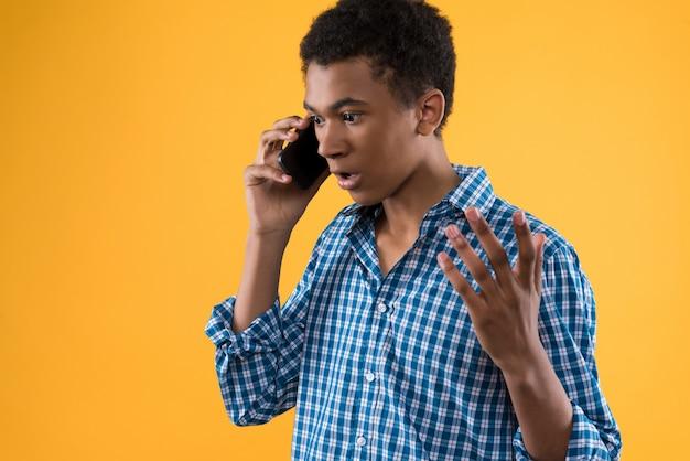 Adolescent afro-américain parle par téléphone cellulaire.