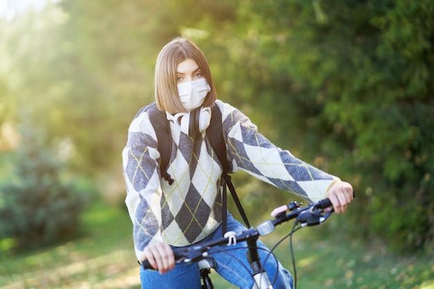 Un adolescent allant à l'école à vélo et portant un masque facial en raison de la pandémie de coronavirus