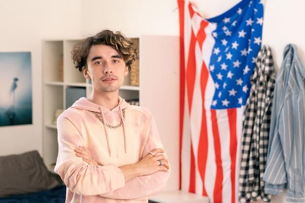 Adolescent américain en tenue décontractée croisant les bras par la poitrine