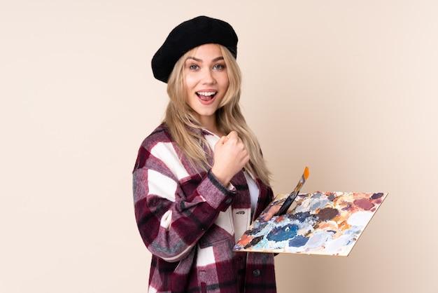 Adolescent artiste femme tenant une palette isolée sur mur bleu célébrant une victoire