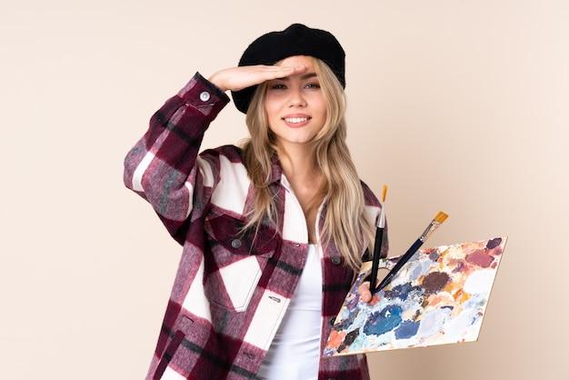 Adolescent artiste fille tenant une palette sur le mur bleu regardant loin avec la main pour regarder quelque chose