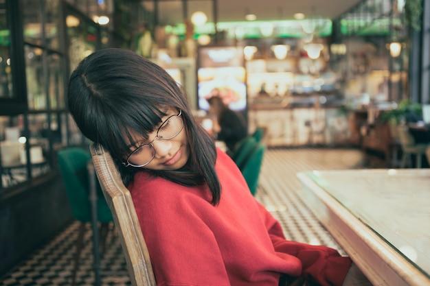 Adolescent asain faire une sieste assis dans une salle de café