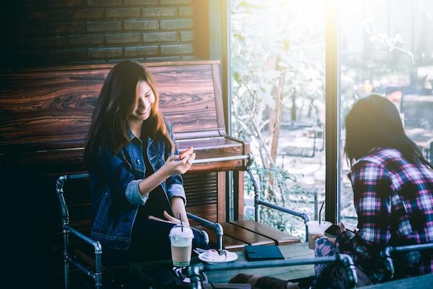 Adolescent asiatique dans le bonheur avec téléphone portable et ami au café
