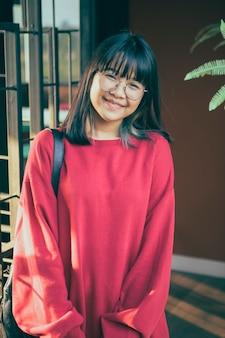 Adolescent asiatique portant décontracté rouge avec visage souriant