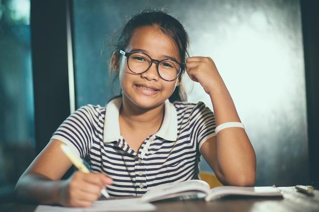 Adolescent asiatique, porter, lunettes, faire, travail maison, à, pile, de, livre scolaire, premier plan