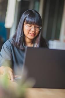 Adolescent asiatique travaillant sur un ordinateur portable dans un salon à la maison