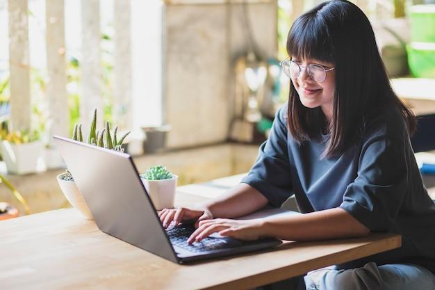 Adolescent asiatique travaillant sur un ordinateur portable dans le salon
