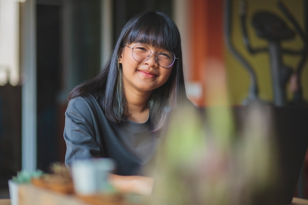 Adolescent asiatique avec un visage souriant à la table de travail de l'ordinateur