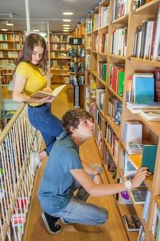 Adolescent assis sur les hanches et en choisissant un livre près de la petite amie