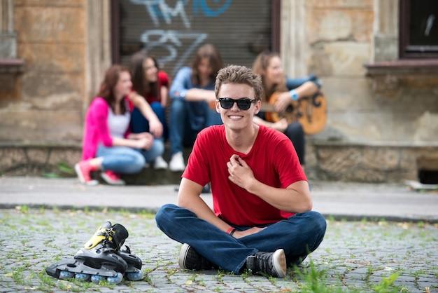 Adolescent assis avec des patins à roues alignées