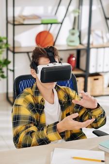 Adolescent assis à sa table et testant une nouvelle application dans un casque de réalité virtuelle