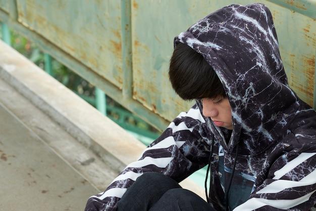 Adolescent assis se baisser la tête. il se sent frustré et dépressif majeur.