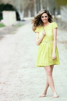 Adolescent aux pieds nus avec une robe jaune