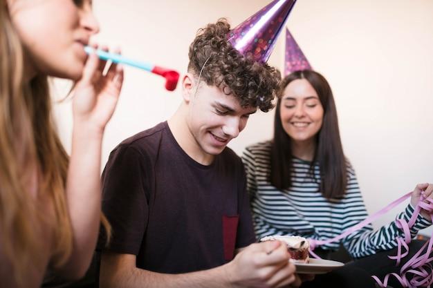 Adolescent ayant gâteau au fromage avec des amis