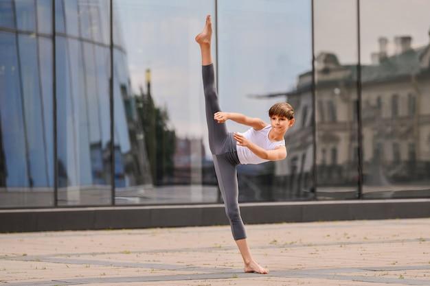 Adolescent de ballet dansant sur fond de reflet de la ville et du ciel dans le mur de verre