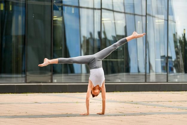 Un adolescent de ballet s'entraîne debout sur ses mains dans le contexte du reflet de la ville et du ciel dans le mur de verre