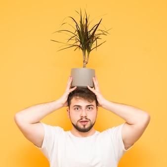 Adolescent avec une barbe tient un pot de fleurs avec une plante sur la tête