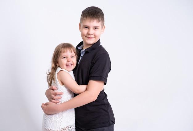 Adolescent beau frère aîné étreignant sa mignonne petite soeur sur fond blanc.