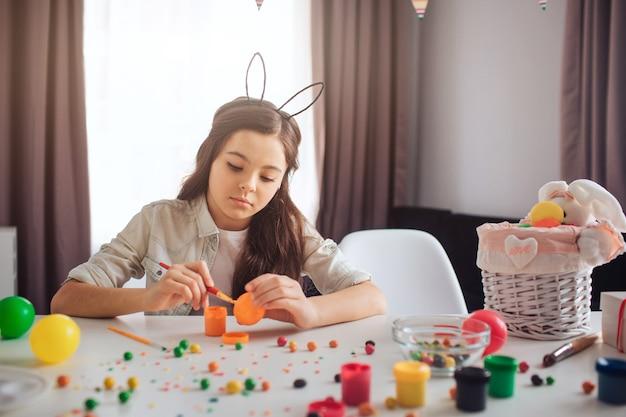 Adolescent bouleversé se prépare pour pâques seul. elle est assise à table et peint des œufs. fille porte des oreilles de lapin. bonbons colorés et décoration sur table.