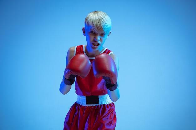 Adolescent en boxe sportswear isolé sur fond bleu studio en néon. boxeur caucasien masculin novice s'entraînant dur et travaillant, coups de pied. sport, mode de vie sain, concept de mouvement.