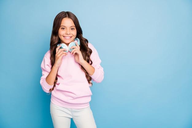 Adolescent brune posant contre le mur bleu