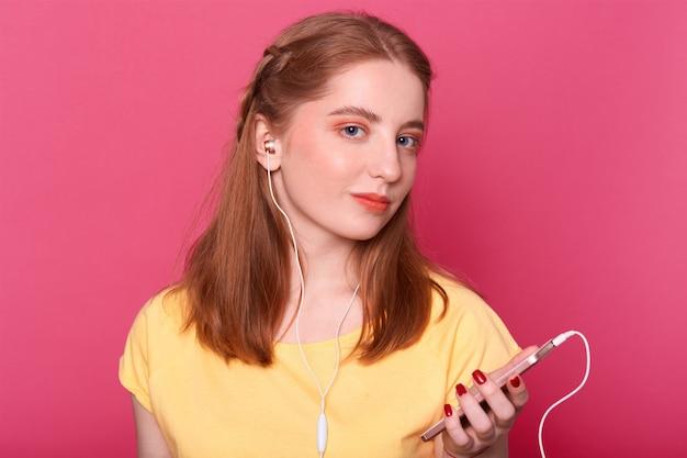 Adolescent carmant, a un téléphone intelligent et des écouteurs, aime écouter de la musique pendant son temps libre, porte des vêtements décontractés