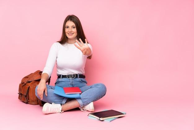 Adolescent caucasien étudiant fille assise sur le sol isolé sur le mur rose heureux et en comptant quatre avec les doigts