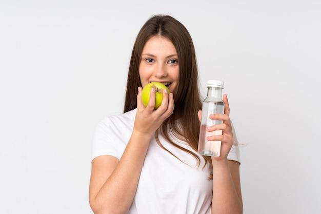 Adolescent, caucasien, girl, isolé, blanc, mur, bouteille, eau, manger, pomme
