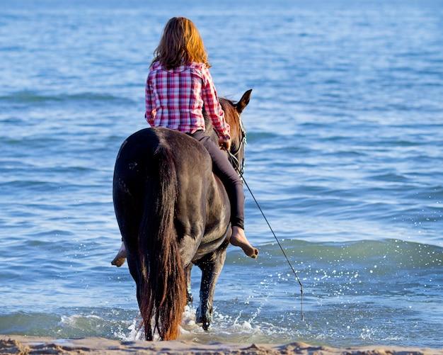 Adolescent et cheval dans la mer
