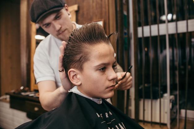 Adolescent coiffeur coupe de cheveux dans le salon de coiffure. coiffure rétro élégante à la mode. portrait d'un enfant avec une belle coupe de cheveux. russie,
